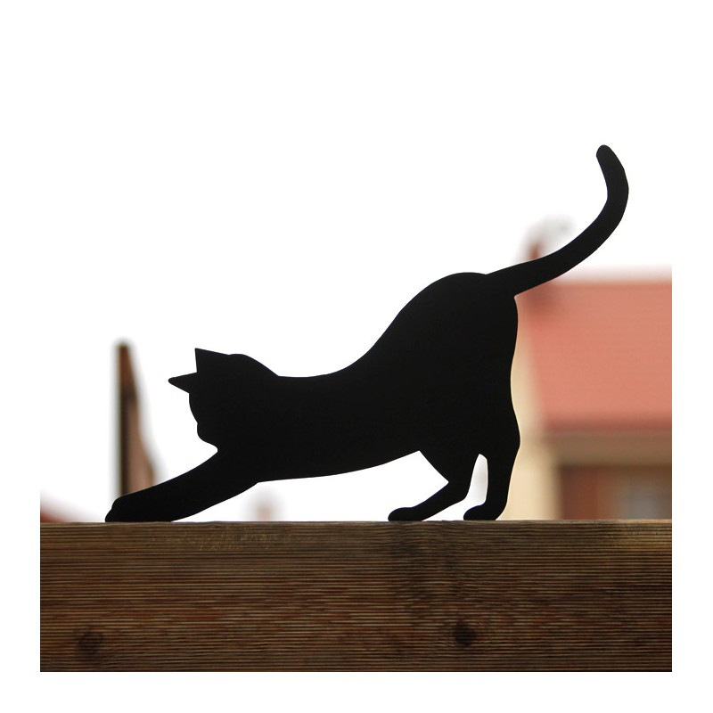 Czarny kot Mizia przykręcony do płotu